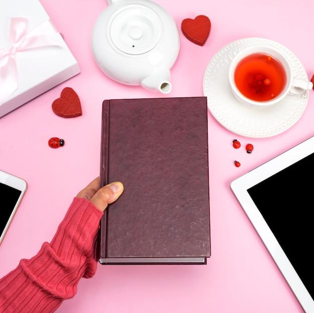 Mão humana feminina detém um livro em uma capa marrom