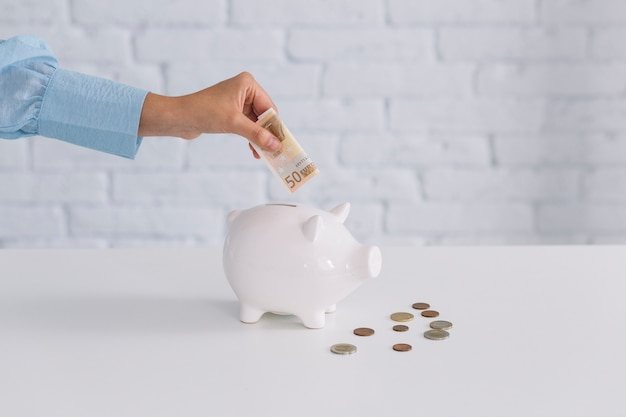 Mão humana, inserindo notas de cinquenta euros em piggybank na mesa