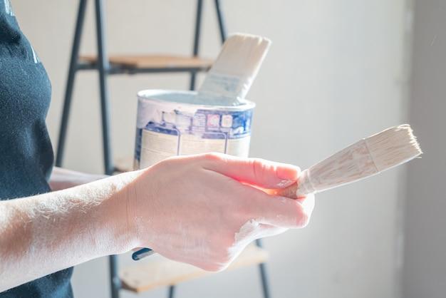 Mão humana manchada com tinta segura o pincel na superfície com uma lata de tinta em pé na escada