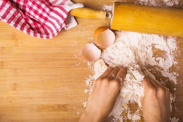 Mão humana, mistura de farinha com ovo na mesa de madeira