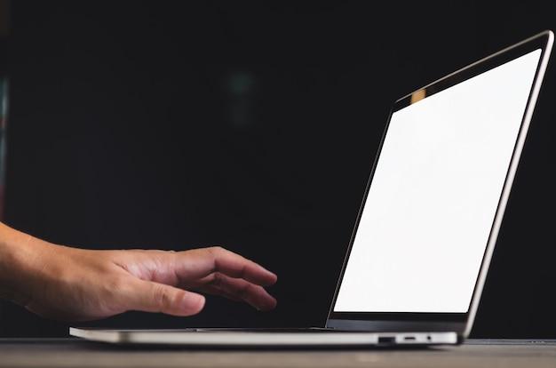 Mão humana na frente do laptop em cima da mesa com imagem em branco, maquete da tela