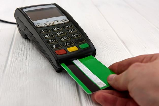 Mão humana pressionando botões no terminal bancário