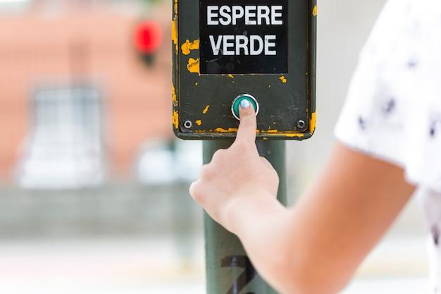 Mão humana, pressionando o sinal de espera verde