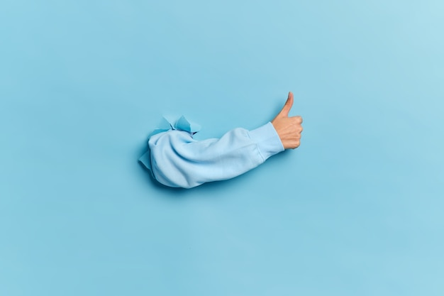 Mão humana rompendo a parede de papel e aparecendo o polegar como sinal de aprovação ou acordo.