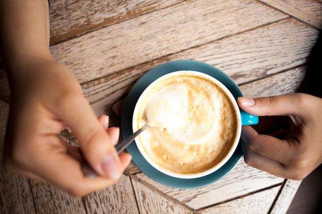 Mão humana segurando a colher de café e mexer o café quente na mesa de madeira