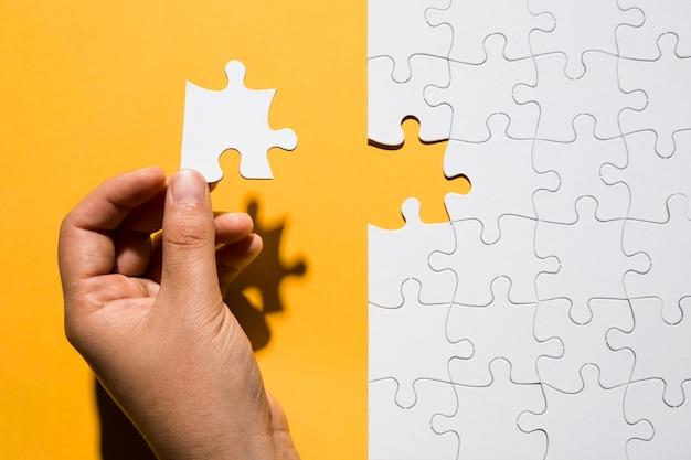 Mão humana segurando a peça do quebra-cabeça sobre grade de quebra-cabeça branca sobre o pano de fundo amarelo