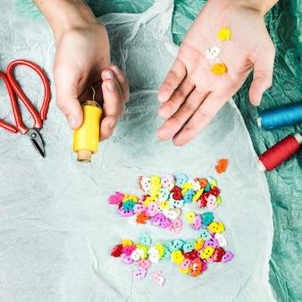 Mão humana segurando botões coloridos e carretel de linha com tesoura