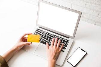 Mão humana, segurando, cartão crédito, e, digitando, ligado, laptop, com, telefone móvel