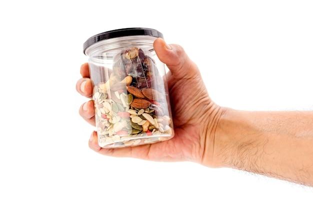 Mão humana segurando grãos inteiros e garrafa de plástico de frutas secas, isolada no fundo branco.