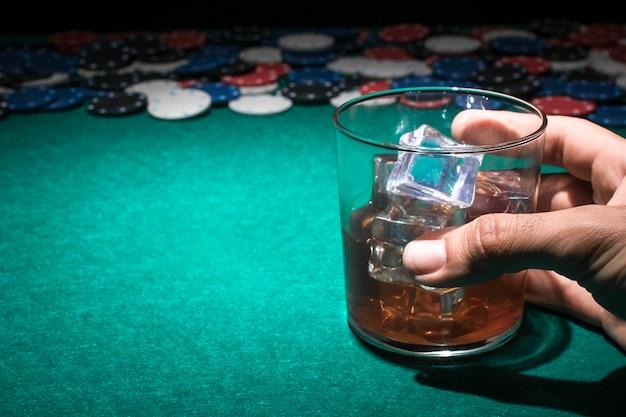 Mão humana segurando o copo de uísque na mesa de poker