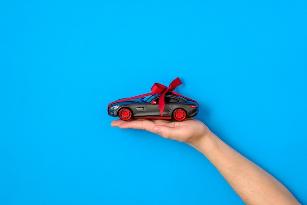 Mão humana segurando o modelo do carro com uma fita vermelha e arco sobre fundo azul. carro como presente ou presente, carro de desenho, chance de ganhar carro moderno, concessionária e locadora, comprar novo conceito de automóvel