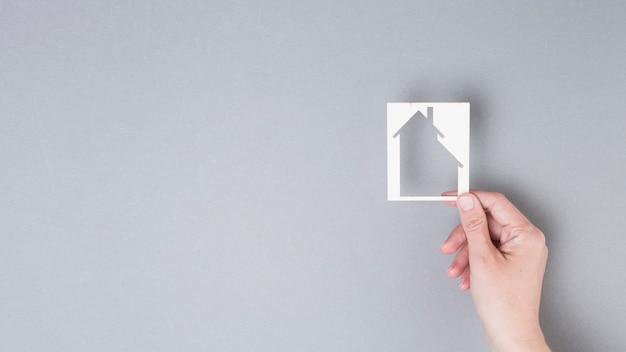 Mão humana segurando o recorte de casa em fundo cinza