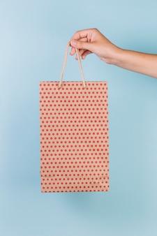 Mão humana segurando o saco de compras de papel padrão pontilhado no fundo azul