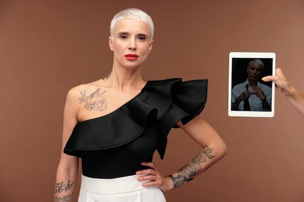Mão humana segurando o touchpad com uma mulher elegante em sua tela na frente de uma mulher transexual loira com tatuagem no peito usando uma regata preta