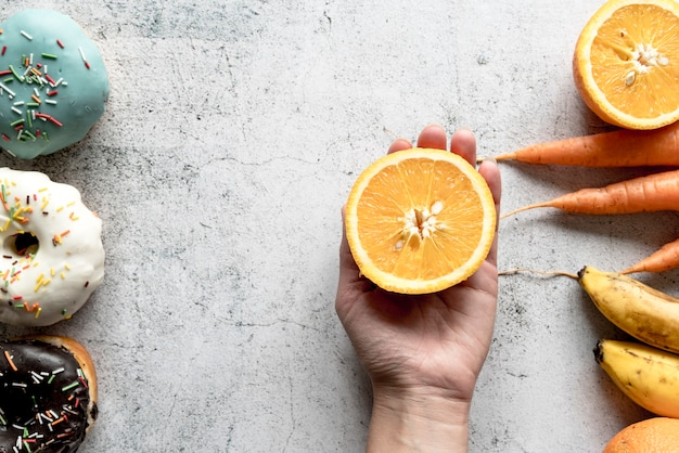 Mão humana segurando pela metade laranja fruta perto de donuts; cenoura e banana