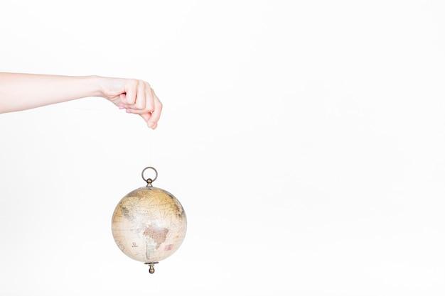Mão humana, segurando, pêndulo globo