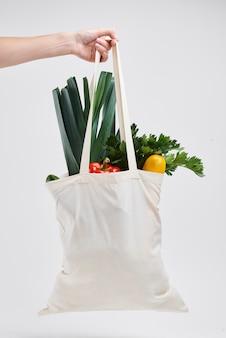 Mão humana segurando sacola de vegetais frescos