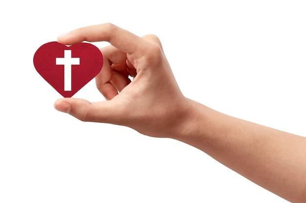 Mão humana segurando um coração vermelho com uma cruz cristã isolada