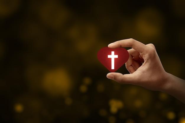 Mão humana segurando um coração vermelho com uma cruz cristã