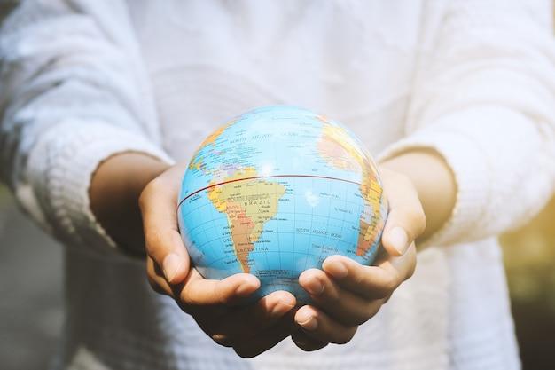 Mão humana segurando um globo com as duas mãos