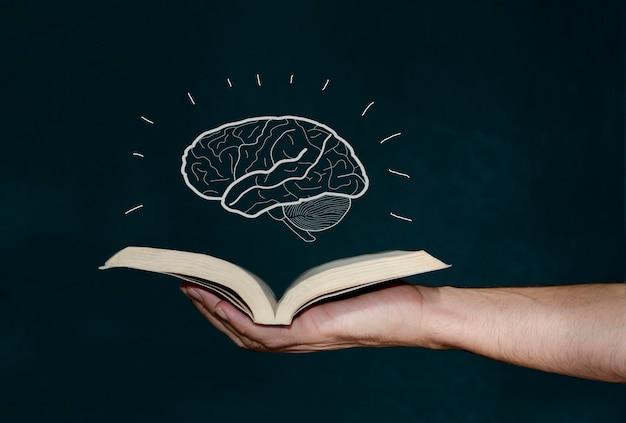 Mão humana segurando um livro com um cérebro no topo conceito de conhecimento