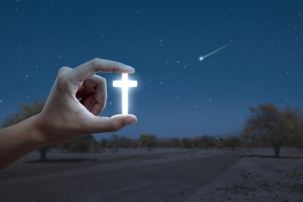 Mão humana segurando uma cruz cristã com o fundo da cena noturna