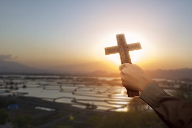 Mão humana segurando uma cruz cristã com um fundo do céu ao nascer do sol