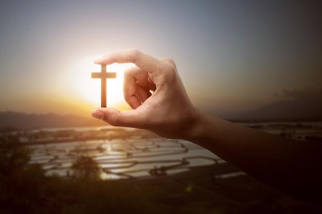 Mão humana segurando uma cruz cristã com um fundo do céu ao pôr do sol