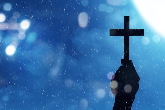 Mão humana segurando uma cruz cristã com uma cena noturna de fundo