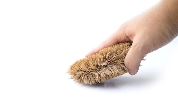Mão humana segurando uma escova de limpeza isolada no branco