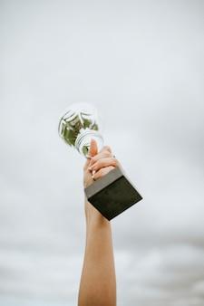 Mão humana segurando uma taça de troféu