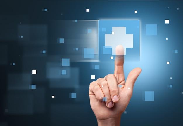 Mão humana tocando a tela com o sinal da cruz médica