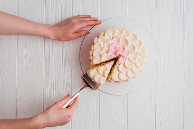 Mão humana tomando um pedaço de bolo