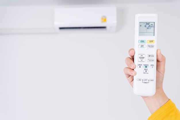 Mão humana usando controle remoto branco para ajustar a temperatura do ar condicionado.