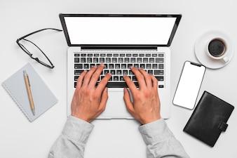 Mão humana usando laptop com smartphone; bloco de anotações; caneta; óculos e xícara de chá na superfície branca