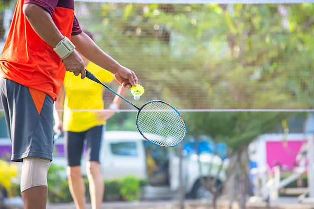 Mão idosa do homem que guarda uma árvore do borrão do fundo da raquete de badminton no parque.