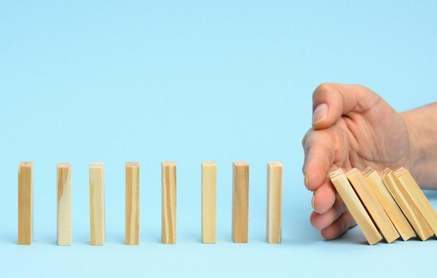 Mão impede a queda de barras de madeira em uma superfície azul