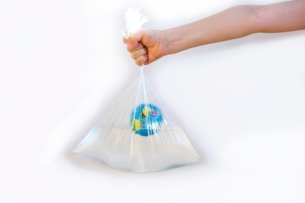 Mão infantil segura um saco plástico com água e um globo