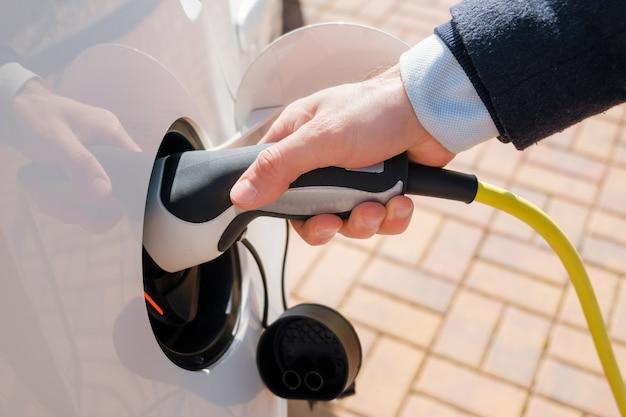 Mão inserindo o cabo de alimentação conectado ao carro elétrico para recarregar