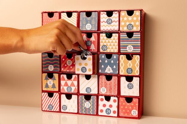 Mão inserir pequenos doces no calendário do advento