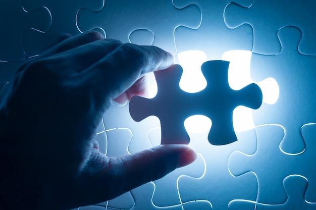 Mão inserir quebra-cabeças, imagem conceitual da estratégia de negócios