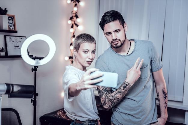 Mão inteira recheada. uma tatuadora loira e seu cliente regular fazendo selfie após uma longa sessão mostrando o trabalho concluído