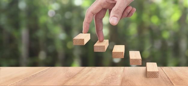 Mão intensificando na escada de madeira de brinquedo
