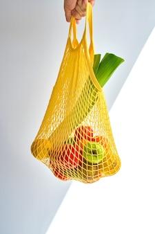 Mão irreconhecível de homem segurando um saco amarelo com uma mistura de frutas e vegetais