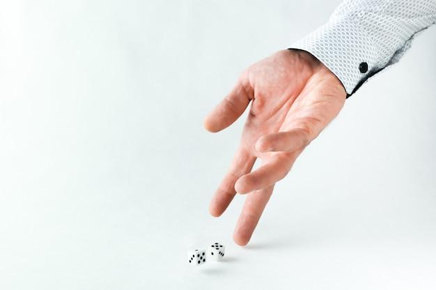 Mão joga dados no fundo branco