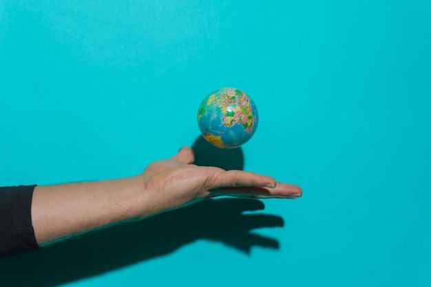 Mão jogando a bola do planeta terra com fundo azul e copie o espaço para o texto