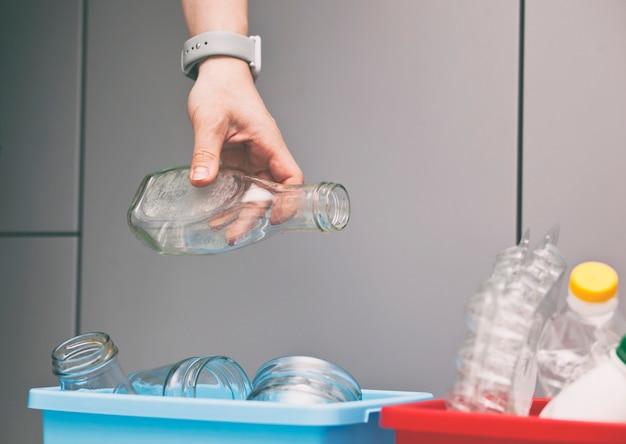 Mão jogando a garrafa de vidro no recipiente para classificar o lixo