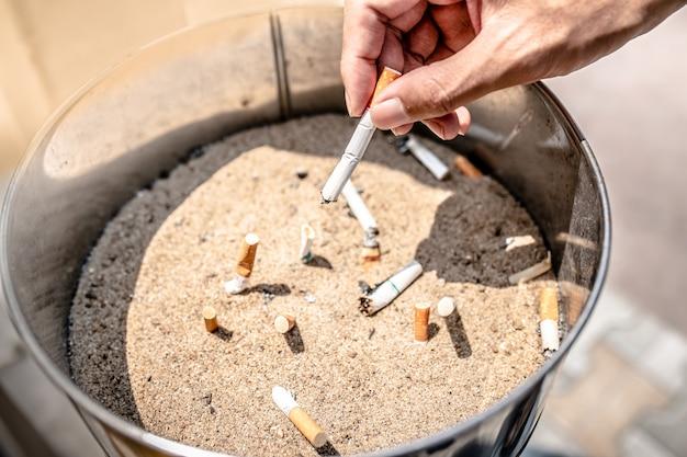 Mão jogando cigarro no cesto de lixo.