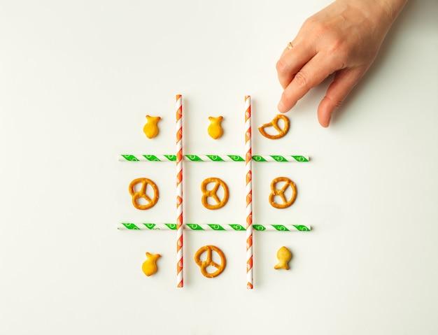 Mão jogando jogo da velha com pequenos biscoitos secos e canudos de papel, layout plano