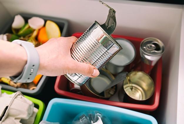 Mão jogando lata para um dos quatro recipientes para classificação de lixo